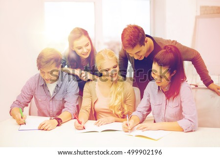 school and education concept - group of smiling students with notebooks at school