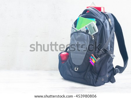 School backpack with supplies on white desktop