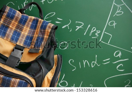 School bag against a school board with mathematical formulas. - stock photo