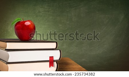 school books and apple against blackboard - stock photo