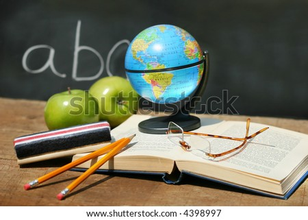 School books and apple in front of school chalkboard with small atlas - stock photo