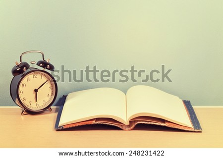 school books and clock on table. - stock photo