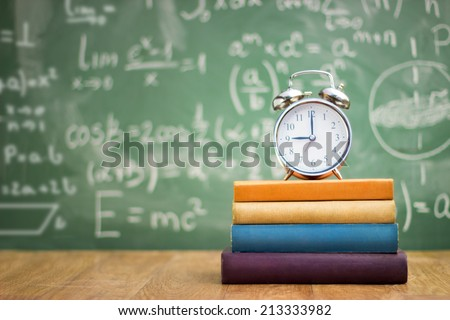 school books with alarm clock on green school board background  - stock photo