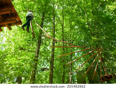 School boy climbing in adventure activity park - stock photo