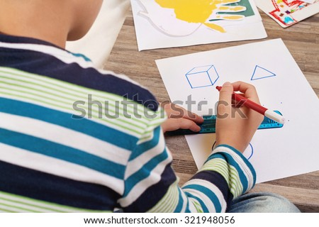 School Boy drawing geometric shapes on paper with Pencil. Kid, homework, education concept - stock photo
