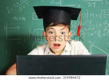 school boy in graduation cap having lesson in computer class - stock photo