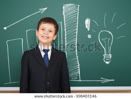 school boy in suit show success graphs on board - stock photo