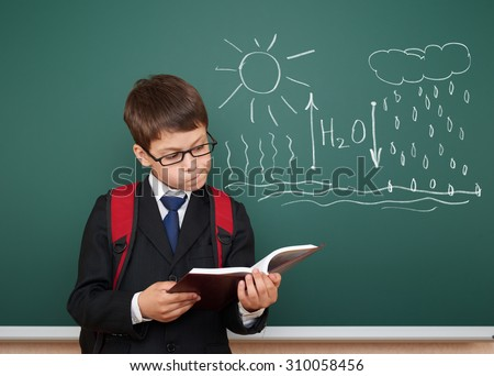 school boy read book about circulation of water  - stock photo