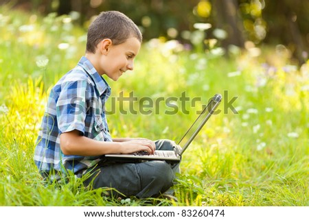 School boy using his laptop outdoor on a meadow - stock photo