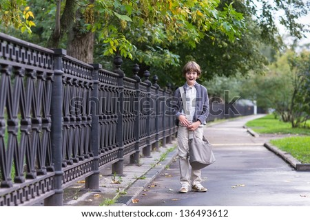 School boy walking home on a rainy autumn day - stock photo