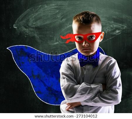school boy wearing a superhero costume with blackboard behind him - stock photo