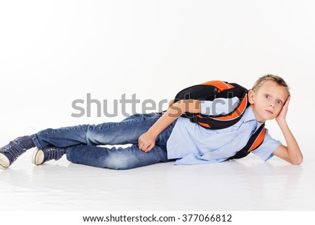 School boy with bag lying on the floor