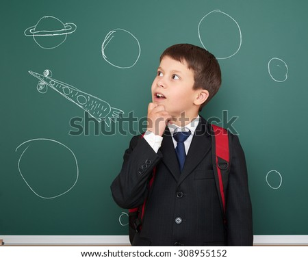 school boy with drawing space rocket on board - stock photo