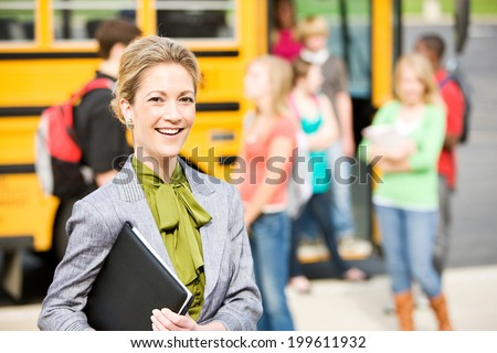 School Bus: Cheerful School Principal With Students In Background - stock photo