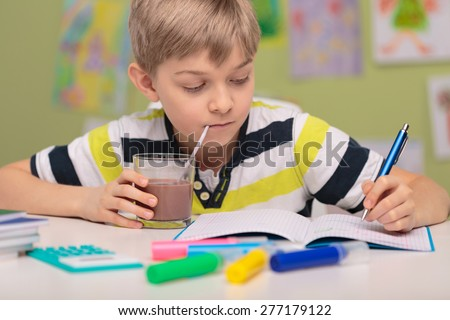 School child doing homework and drinking cacao - stock photo