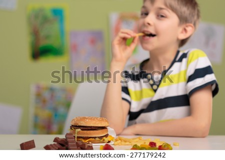 School child eating unhealthy snacks for lunch - stock photo