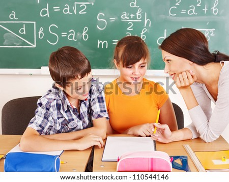 School child with teacher in classroom. - stock photo