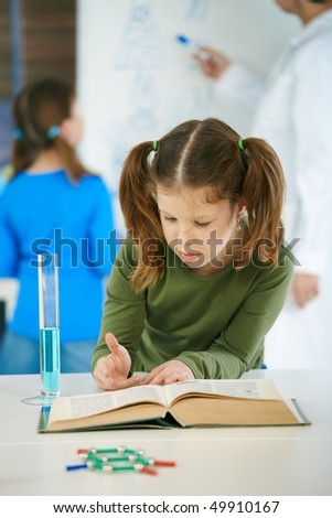 School children and teacher in classroom at elementary school in science class. - stock photo