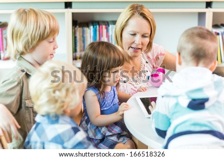 School children with female teacher using digital tablet in library - stock photo