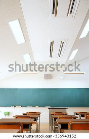 School classroom with school desks and blackboard in Japanese high school - stock photo
