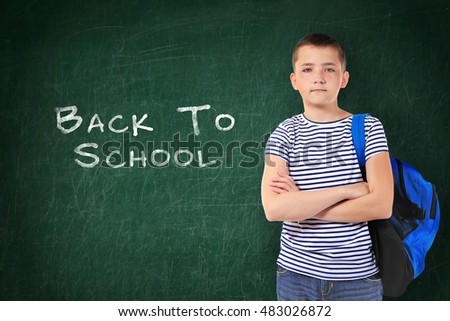 School concept. Cute boy standing on blackboard background. Text back to school.