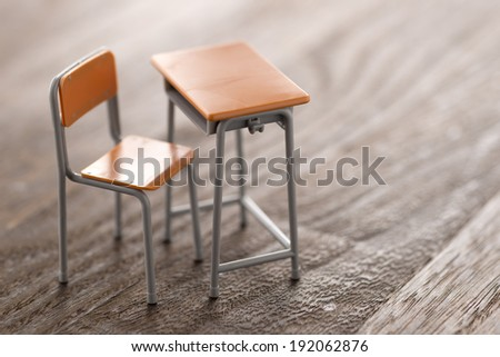 school desk on wooden background - stock photo