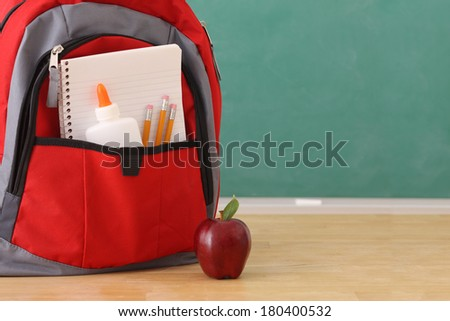 School education still life, backpack full of school supplies and red apple - stock photo