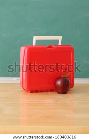 School education still life with apple and luch box, chalkboard background - stock photo