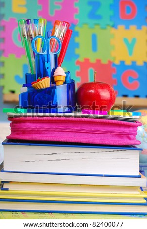 school equipment and apple on the desk in the classroom - stock photo