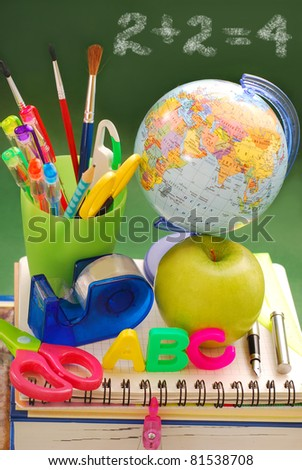 school equipment ,apple and globe against to  green chalkboard - stock photo