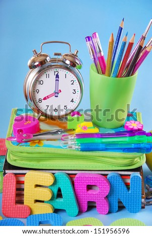 school equipment with alarm clock,books,notes,pencils and apple on blue background - stock photo