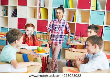 School friends playing â??Who I amâ?? during break in classroom - stock photo
