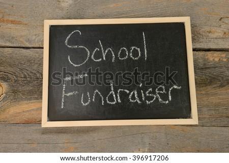 school fundraiser written in chalk on a chalkboard on a rustic background - stock photo