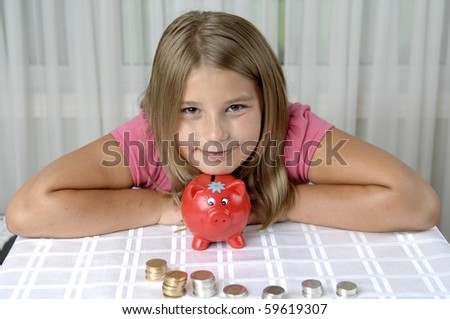 School girl count coins before dropping them into the piggy bank. - stock photo