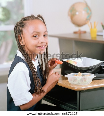 School girl eating a packed lunch at her desk - stock photo