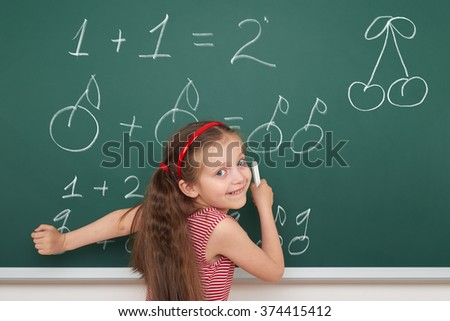 school girl exercise math from fruits on board - stock photo