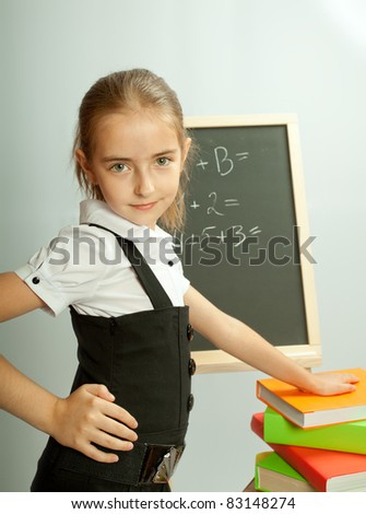 School girl front blackboard with hand on stack of books.