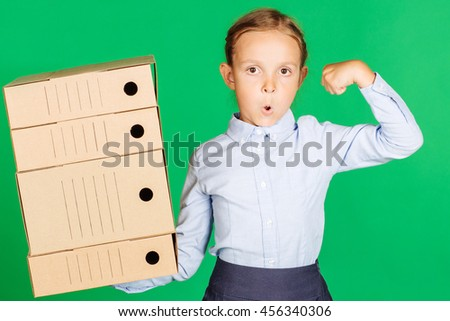 school girl in a school uniform with folder or box and showing her biceps. Learning and school concept. Image on chromakey background. - stock photo