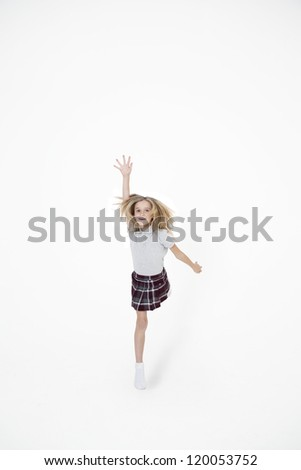 School girl jumping with hand raised over white background - stock photo