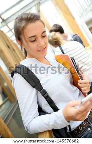 School girl sending message with smartphone - stock photo