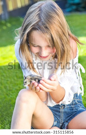 School girl sitting in the backyard with a small hamster in palms - stock photo