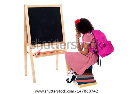 School girl sitting on stack of books and wondering - stock photo