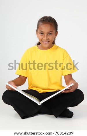 School girl sitting reading a book