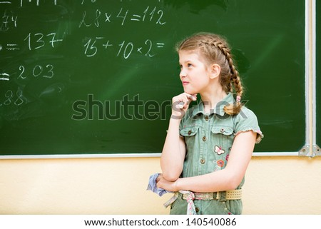 School girl thinking at blackboard in classroom - stock photo