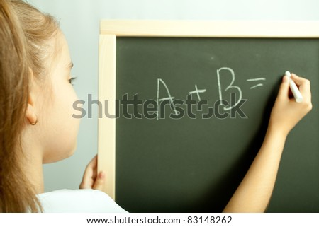 School girl write exercise on the black board in the class - stock photo