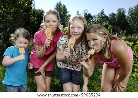 School girls eat popsicle in the backyard. - stock photo