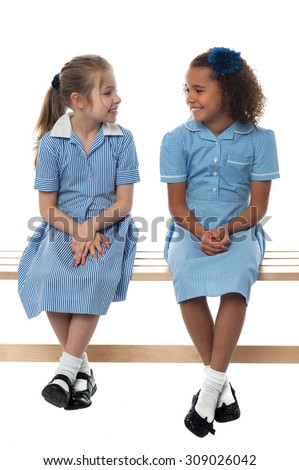 School girls sitting on bench, talking together - stock photo