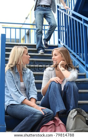 School girls talking on steps - stock photo