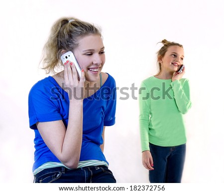 School girls talking on their cell phones - stock photo