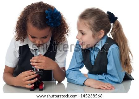 School girls using a microscope in lab - stock photo